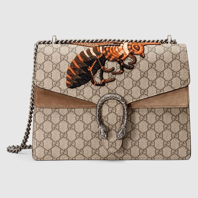 An embroidered GG supreme canvas bag with our textured tiger head closure-a unique detail referencing the Greek god Dionysus, who in myth is said to have crossed the river Tigris on a tiger sent to him by Zeus. The sliding chain strap can be worn multiple ways, changing between a shoulder and a top handle bag. Using brass thread wrapped in silk, the bee is hand-embroidered on to silk then applied to the front.
