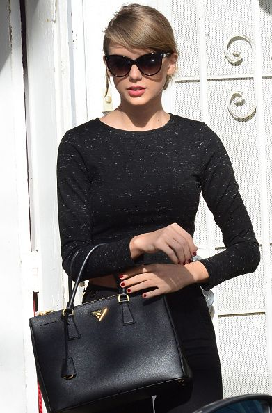 Taylor Swift out in Los Angeles carrying a classic Prada Saffiano black leather tote bag
